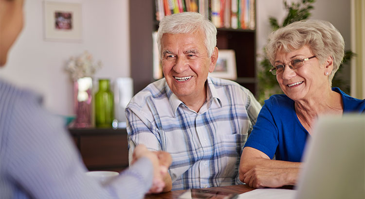 older couple shaking hands with realtor