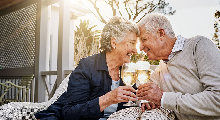 older couple toasting to the sell of their home