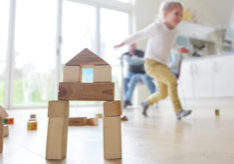 Family at home, child playing with building blocks