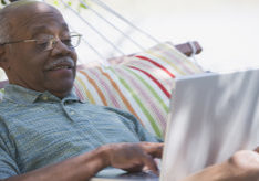 Senior African man using laptop in hammock