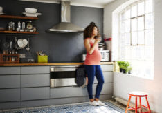 A pregnant woman drinks a cup of coffee whilst looking out of her modern kitchen on a sunny day