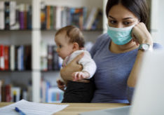 Worried mother with face protective mask working from home